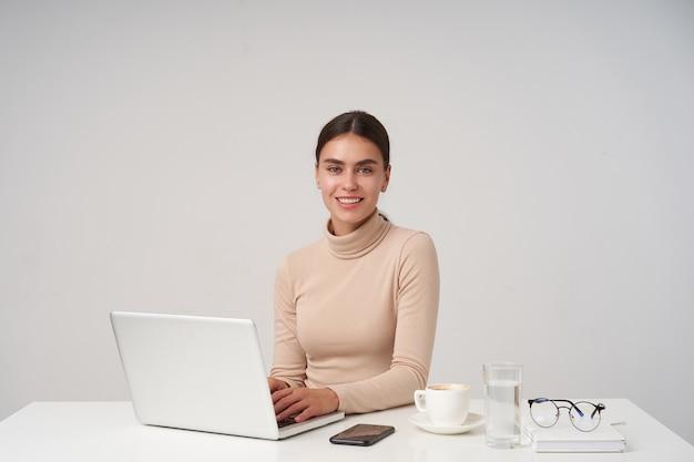 Foto interior de una mujer joven y bonita morena alegre que muestra sus dientes blancos perfectos mientras sonríe positivamente, escribiendo texto en el teclado mientras posa sobre una pared blanca