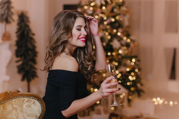 Foto interior de una mujer joven impresionante con manicura elegante que expresa emociones felices en año nuevo. chica atractiva con peinado rizado disfrutando de la fiesta de navidad en casa.