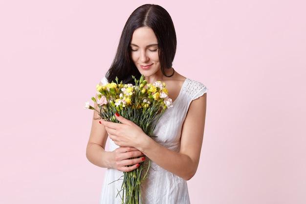 La foto interior de la mujer morena mira suavemente las flores en sus manos, vestida con un vestido blanco, presente de su novio, posando aislada en rosa. copiar espacio para contenido de promoción.