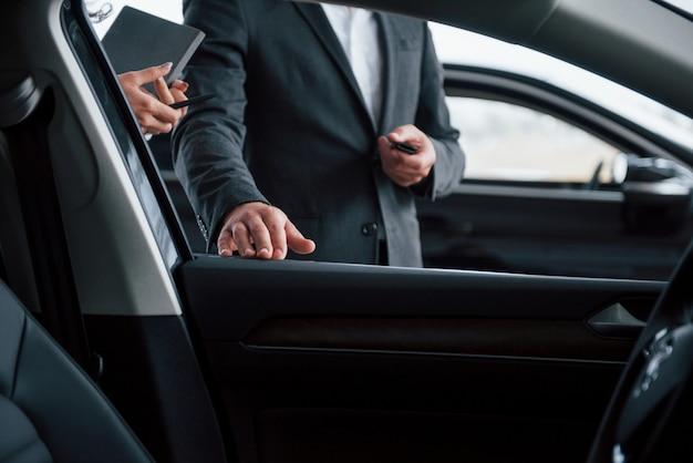 Foto del interior del vehículo. clienta y empresario barbudo con estilo moderno en el salón del automóvil