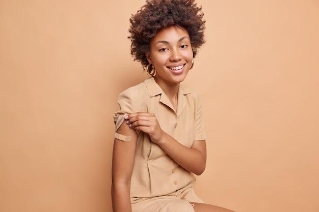 Foto en interiores de una mujer positiva con cabello rizado que muestra el brazo vacunado con yeso recibe una segunda dosis de vacuna feliz de sentirse protegido levanta la manga del vestido aislado sobre una pared beige