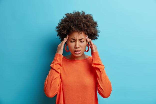 Foto de joven afroamericana frustrada tiene dolor de cabeza mantiene las manos en las sienes sufre migraña insoportable
