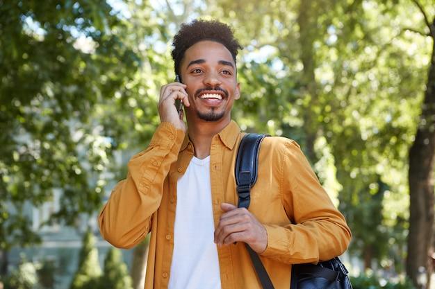 Foto de joven afroamericano alegre con camisa amarilla, caminando en el parque, hablando por teléfono inteligente, esperando a su amigo, mirando a otro lado y sonriendo ampliamente.