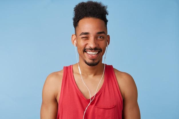 Foto de joven afroamericano feliz sostiene, escucha canciones geniales, viste con una camiseta roja, mira y guiña un ojo, se para.