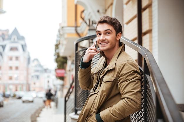 Foto de joven alegre caminando por la calle y mirando a un lado mientras habla por su teléfono.