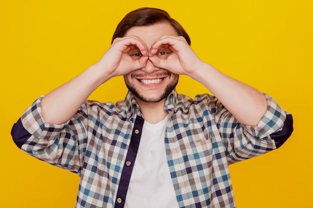 Foto de joven alegre emocionado mostrar los dedos binoculares ok okey signo aislado sobre fondo de color amarillo