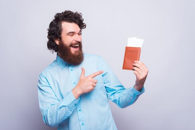 Foto de un joven alegre sosteniendo un pasaporte con algunos boletos y señalándolos cerca de una pared gris