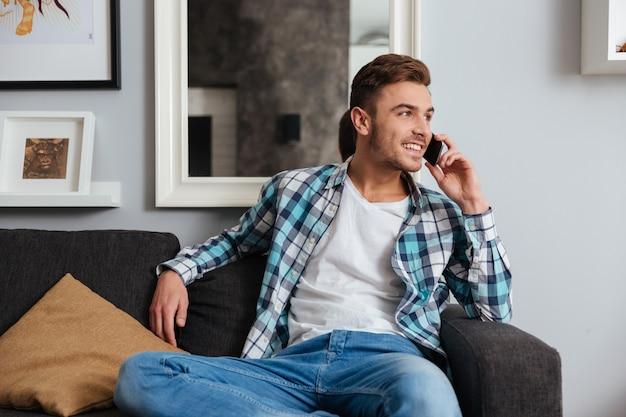 Foto de joven alegre vestido con camisa en una jaula de impresión sentado en el sofá en casa y hablando por su teléfono.