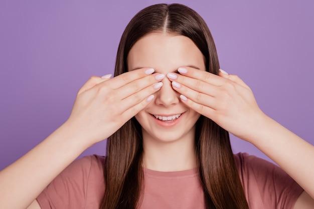 Foto de joven atractiva chica de cabello castaño con las manos cerrar los ojos de la cubierta aislado sobre fondo violeta