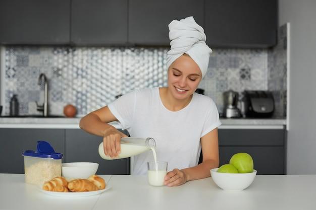 Foto de joven atractiva mujer rubia sentada en la mesa por la mañana, sonriendo, mira un vaso de leche