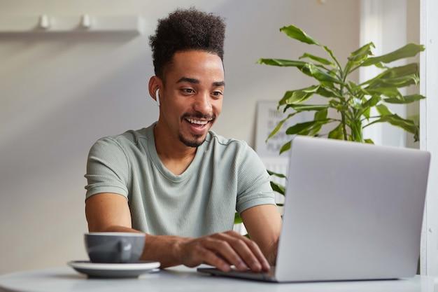 Foto de joven atractivo afroamericano alegre, trabaja en una computadora portátil, se sienta en un café, mira el monitor y sonríe ampliamente, charlando con su novia.
