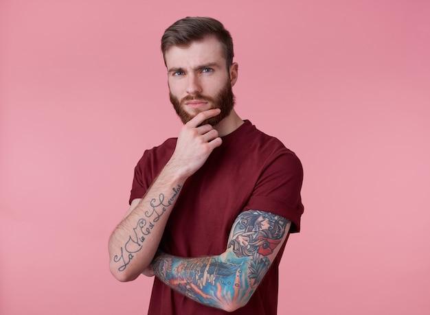 Foto de joven atractivo pensamiento tatuado hombre barbudo rojo en camiseta roja, se encuentra sobre fondo rosa, mira a la cámara y toca la barbilla.