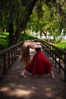 Foto de una joven bailarina de danza del vientre en un parque.
