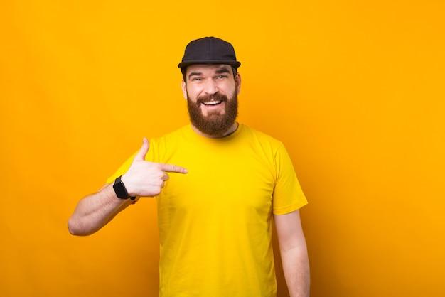 Foto de joven barbudo con camisa amarilla apuntando a él
