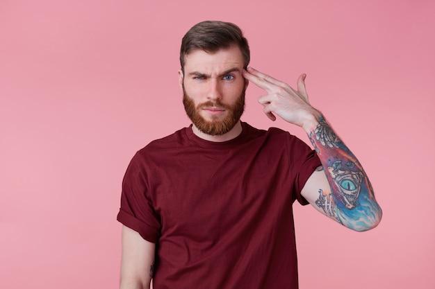 Foto de joven barbudo entintado aislado sobre fondo rosa, disparándole a la cabeza con una pistola de mano, mostrando un gesto de suicidio.