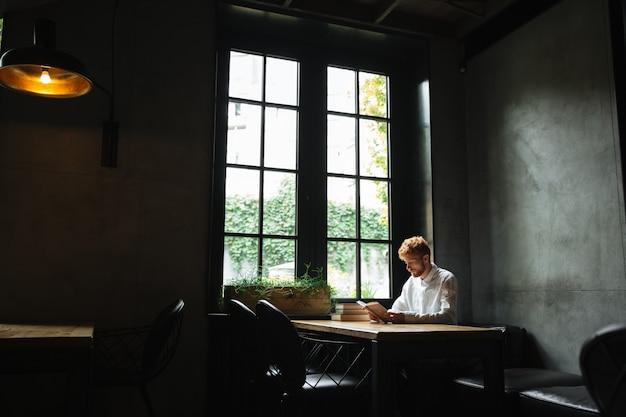 Foto del joven barbudo pelirrojo con camisa blanca leyendo un libro en la cafetería