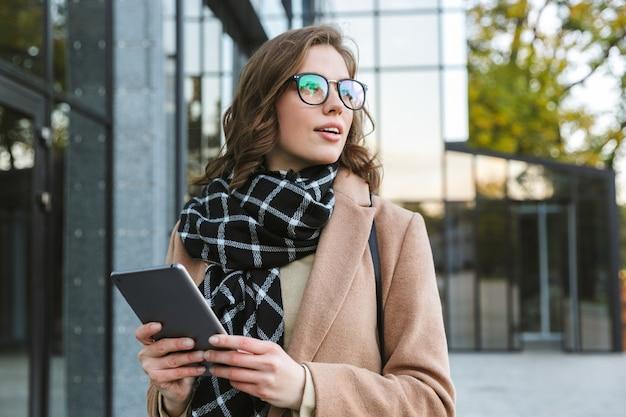 Foto de una joven y bella mujer al aire libre caminando por la calle con tablet pc.