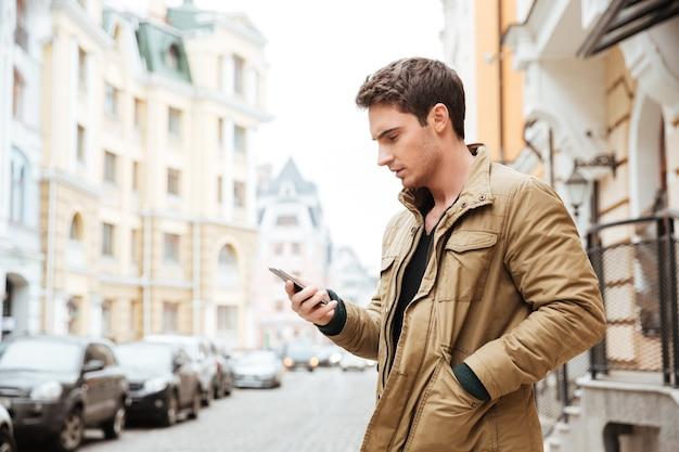 Foto de joven caminando por la calle y charlando por su teléfono al aire libre. mira el teléfono.