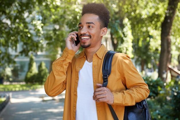 Foto de joven estudiante afroamericano sonriente caminando en el parque, hablando por teléfono inteligente, esperando a su amigo, viste con camisa amarilla, mirando a otro lado y sonriendo ampliamente.