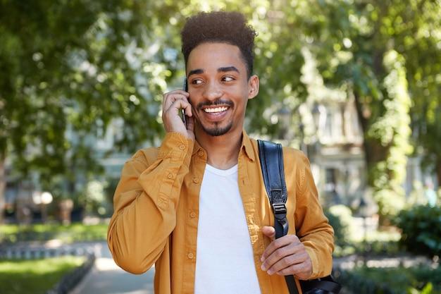 Foto de joven estudiante afroamericano sonriente con camisa amarilla, caminando en el parque, hablando por teléfono inteligente, esperando a su amigo, mirando a otro lado y sonriendo ampliamente.