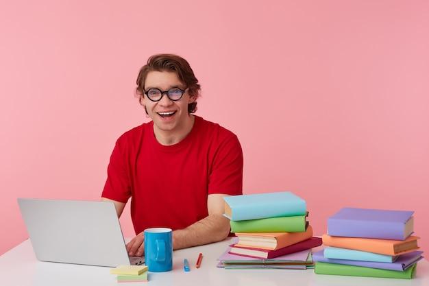 Foto de joven estudiante feliz con gafas viste camiseta roja, el hombre se sienta junto a la mesa y trabaja con una computadora portátil y libros, sonríe ampliamente, se ve feliz, aislado sobre fondo rosa.