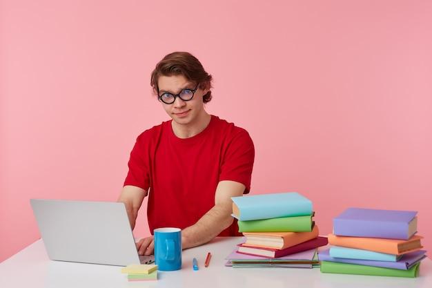 Foto de joven estudiante con gafas viste camiseta roja, el hombre se sienta junto a la mesa y trabaja con una computadora portátil y libros, aislado sobre fondo rosa. parece disgustado e infeliz.