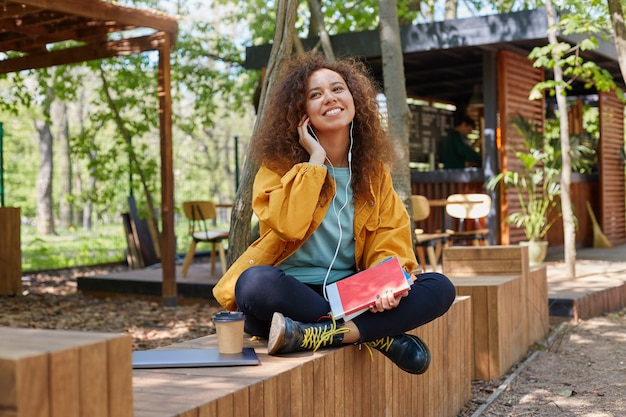 Foto de una joven estudiante rizada de piel oscura sonriente ubicada en la terraza de un café, vestida con abrigo amarillo, disfrutando de la música en auriculares.