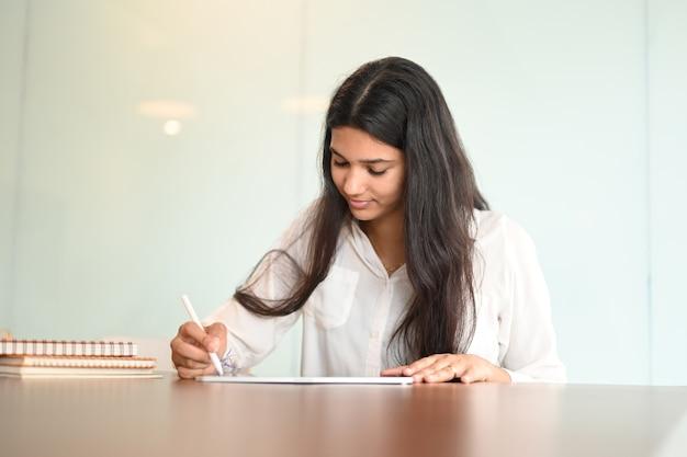 Foto de joven estudiante sentada en la mesa y con lápiz óptico escribiendo en tableta en casa moderna.