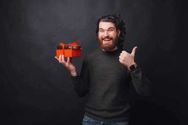 Foto de un joven feliz sosteniendo un regalo y mirando está sonriendo