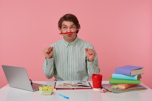 Foto de joven gracioso con gafas, sentado en una mesa con libros, trabajando en una computadora portátil, mira hacia arriba y sostiene el lápiz en los labios, con los puños hacia arriba, aislado sobre fondo rosa.