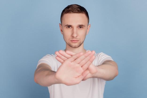 Foto de joven guapo infeliz triste manos cruzadas sin señal de stop declive rechazar aislado sobre fondo de color azul