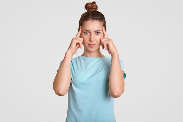 La foto de una joven modelo concentrada intenta concentrarse en la información necesaria, mantiene ambos dedos índices en las sienes, tiene mala memoria, se viste con ropa casual, aislado sobre la pared blanca