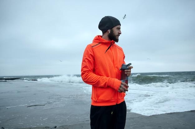 Foto de joven morena activa con barba sosteniendo una botella con agua en las manos mientras mira pensativamente en el mar tormentoso, comenzando el día de trote matutino antes de su trabajo