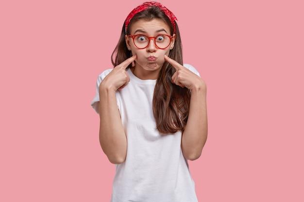 Foto de joven mujer caucásica sopla mejillas, hace muecas, apunta a la cara, usa diadema, camiseta blanca casual