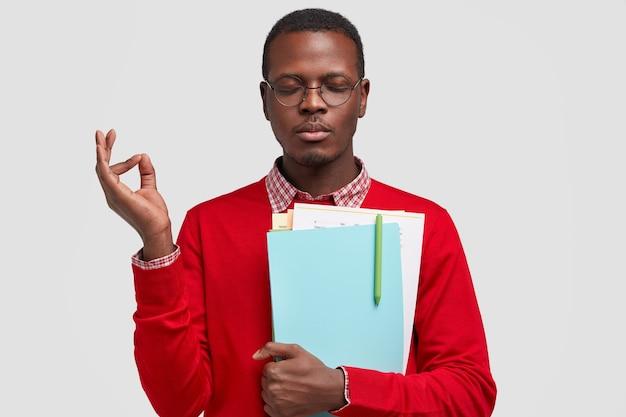 Foto de un joven negro concentrado que medita en el interior, hace un gesto aceptable, lleva un bloc de notas con un bolígrafo