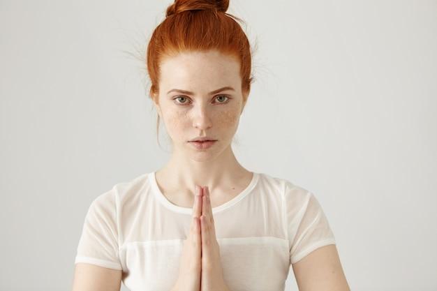 Foto de joven pelirroja pecosa, mujer caucásica posando con las manos juntas en namaste mientras practica yoga en la pared blanca de la mañana, concentrando una expresión tranquila en su rostro