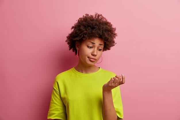 Foto de una joven poco impresionada que mira su nueva manicura, no le gustan las uñas pulidas, vestida con una camiseta verde brillante, aislada en la pared rosa. la dama mira atentamente los dedos