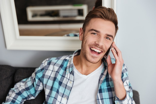 Foto de joven riendo vestido con camisa en una jaula de impresión sentado en el sofá en casa y hablando por su teléfono.