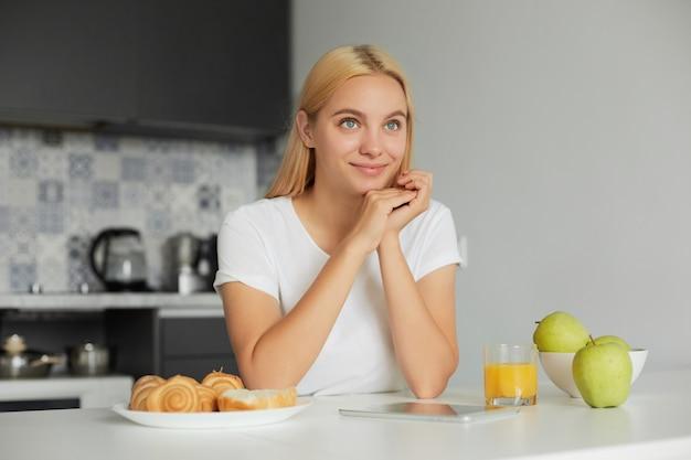Foto de joven rubia sentada en la mesa de la cocina por la mañana, sonriendo