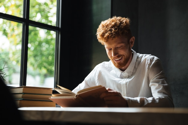 Foto de joven sonriente barbudo pelirrojo en camisa blanca leyendo libro