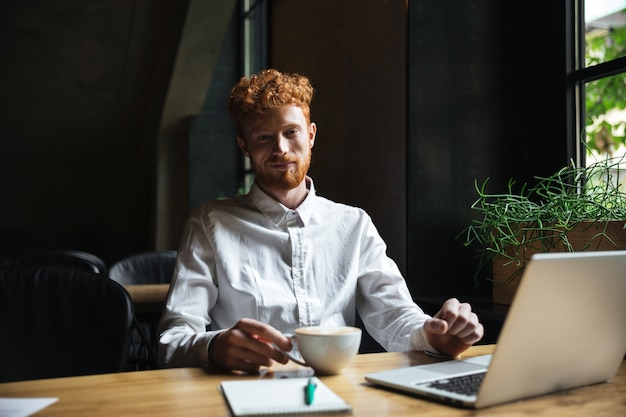 Foto de joven sonriente barbudo pelirrojo sosteniendo una taza de café en la cafetería