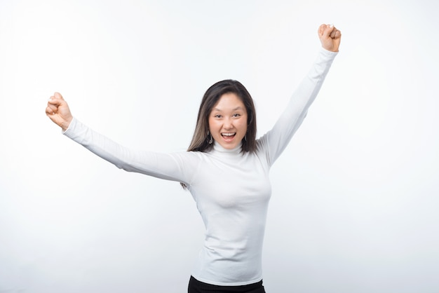 Foto de joven sorprendida celebrando el éxito con los brazos arriba sobre fondo blanco.
