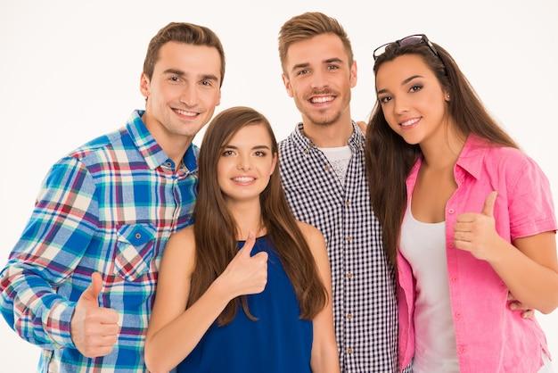 Foto de jóvenes alegres de pie mostrando los pulgares para arriba