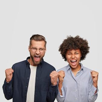 Foto de jóvenes estudiantes de raza mixta enojados aprietan los puños con molestia, gritan desesperadamente