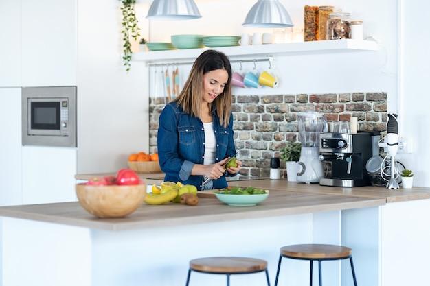 Foto de kiwi de corte de mujer joven y bonita para preparar bebidas de desintoxicación en la cocina de casa.