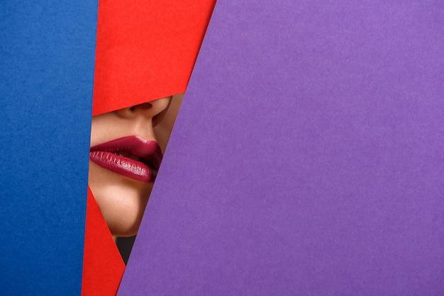 Foto de los labios de la modelo rodeados por láminas de cartón de contraste.