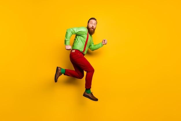 Foto lateral de perfil de cuerpo completo del hombre asombrado saltar, correr, prisa, increíbles descuentos, mirar estupor, usar pantalones de tirantes aislados sobre color de brillo