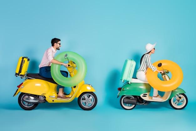 Foto lateral de perfil de longitud completa de dos personas positivas aman novios, esposo, esposa, conductor, ciclista, paseo en moto, camino a las vacaciones de verano, fin de semana, luna de miel, mar, aislado sobre pared de color azul