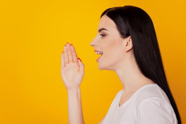Foto lateral de perfil de manos de mujer joven y atractiva cerca de la boca decir decir noticias gritar anuncio aislado sobre fondo de color amarillo