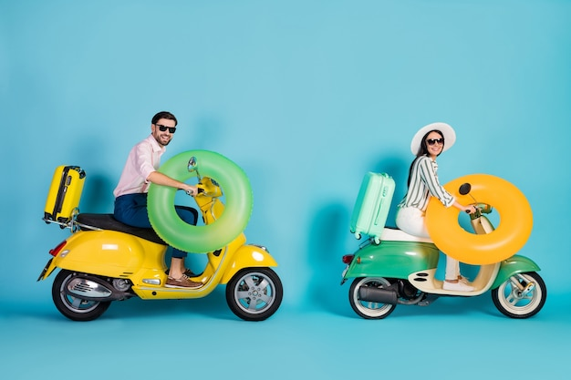 Foto lateral de perfil de tamaño completo positivo dos personas motociclistas jinete conductor conducir moto camino a verano mar aventura resort de vacaciones mantenga salvavidas equipaje aislado pared de color azul